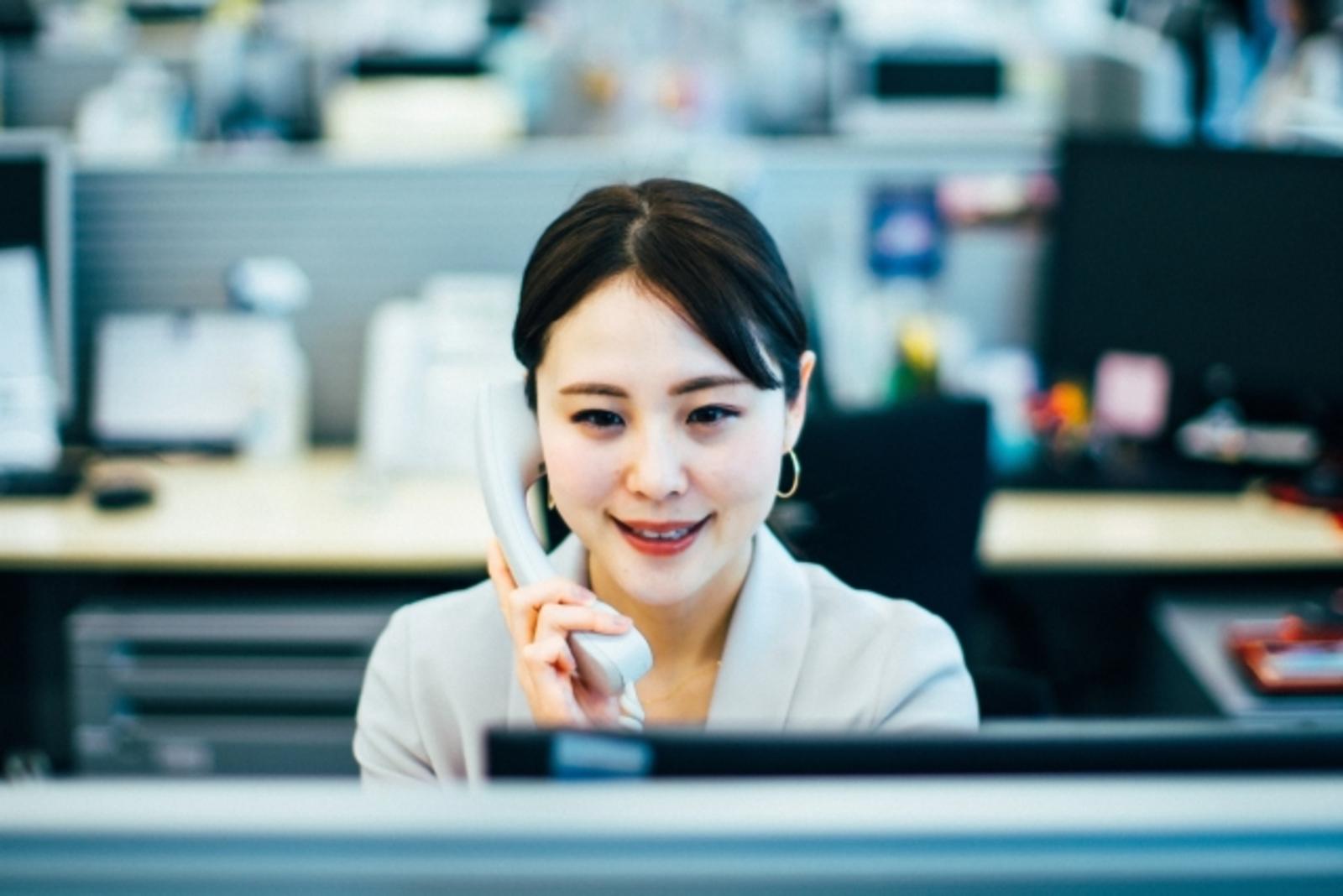 職場で電話をしている女性の画像