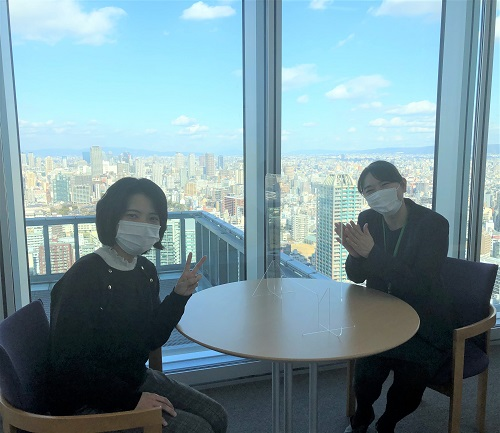 晴天の大阪市街を一望できるノアあべのハルカス校教室窓際のテーブルで笑顔のTさんとしもの