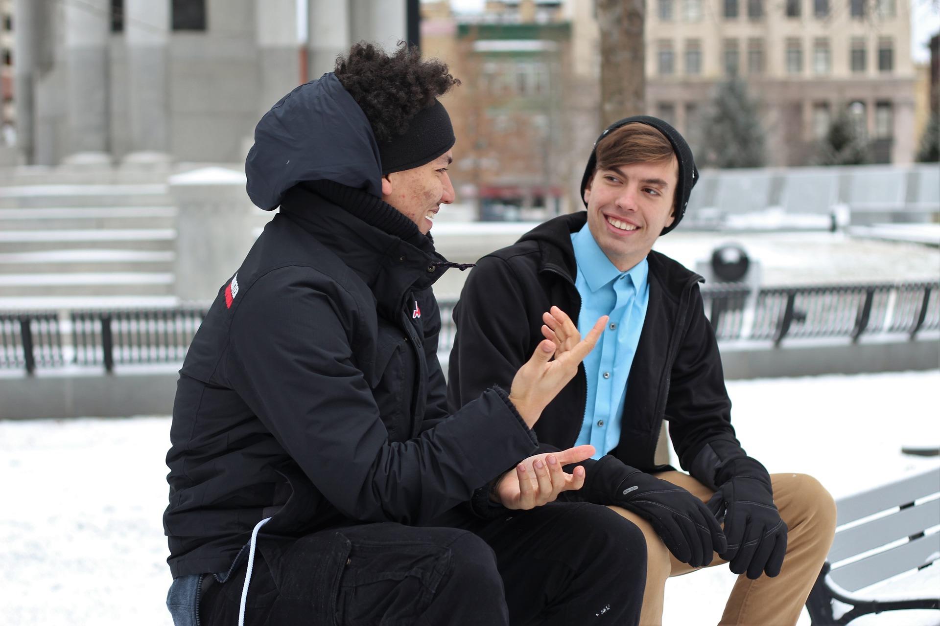 二人の男性がベンチに腰をかけて会話をしている様子