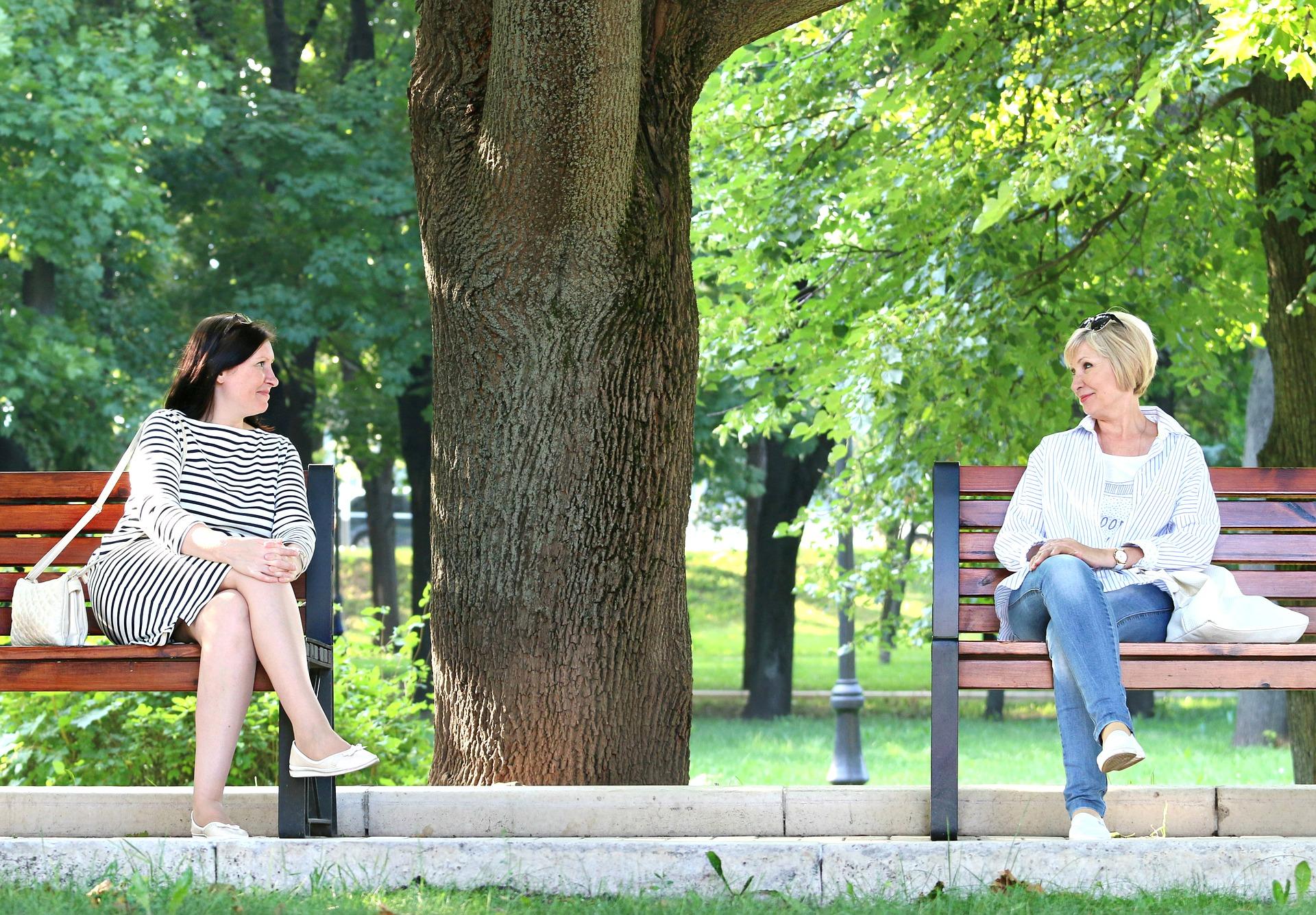 異なるベンチに座っている二人の女性が会話をしている様子