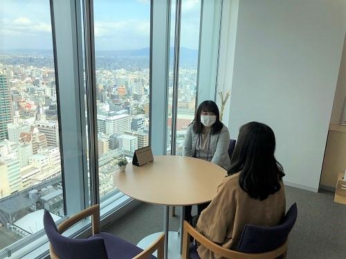 ノアあべのハルカス校の大阪市内を一望できる窓際でインタビューするMさんとまつだ