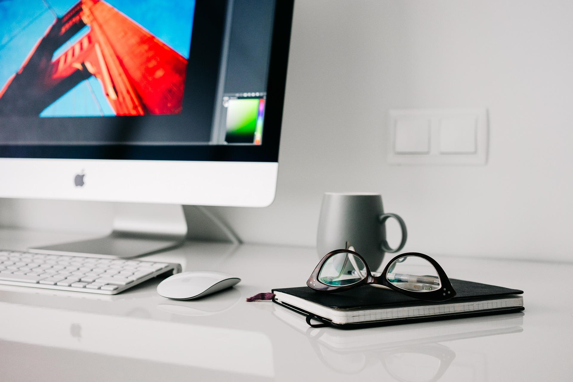 パソコンのキーボードの横に置いてある手帳の上にメガネが置かれている
