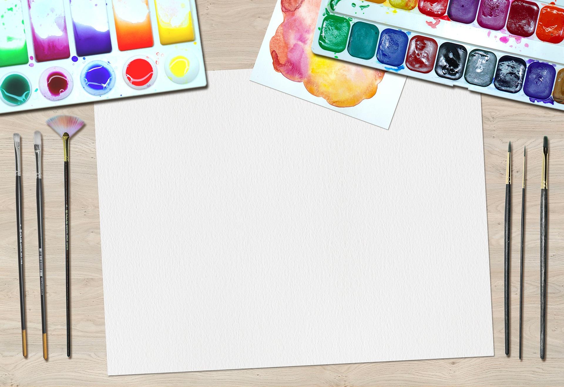 机の上に白紙の紙と絵具が準備されている