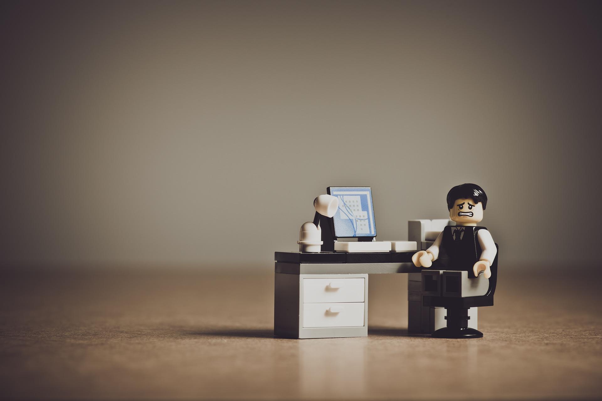 LEGOの男性がデスクに座り険しい表情をしている