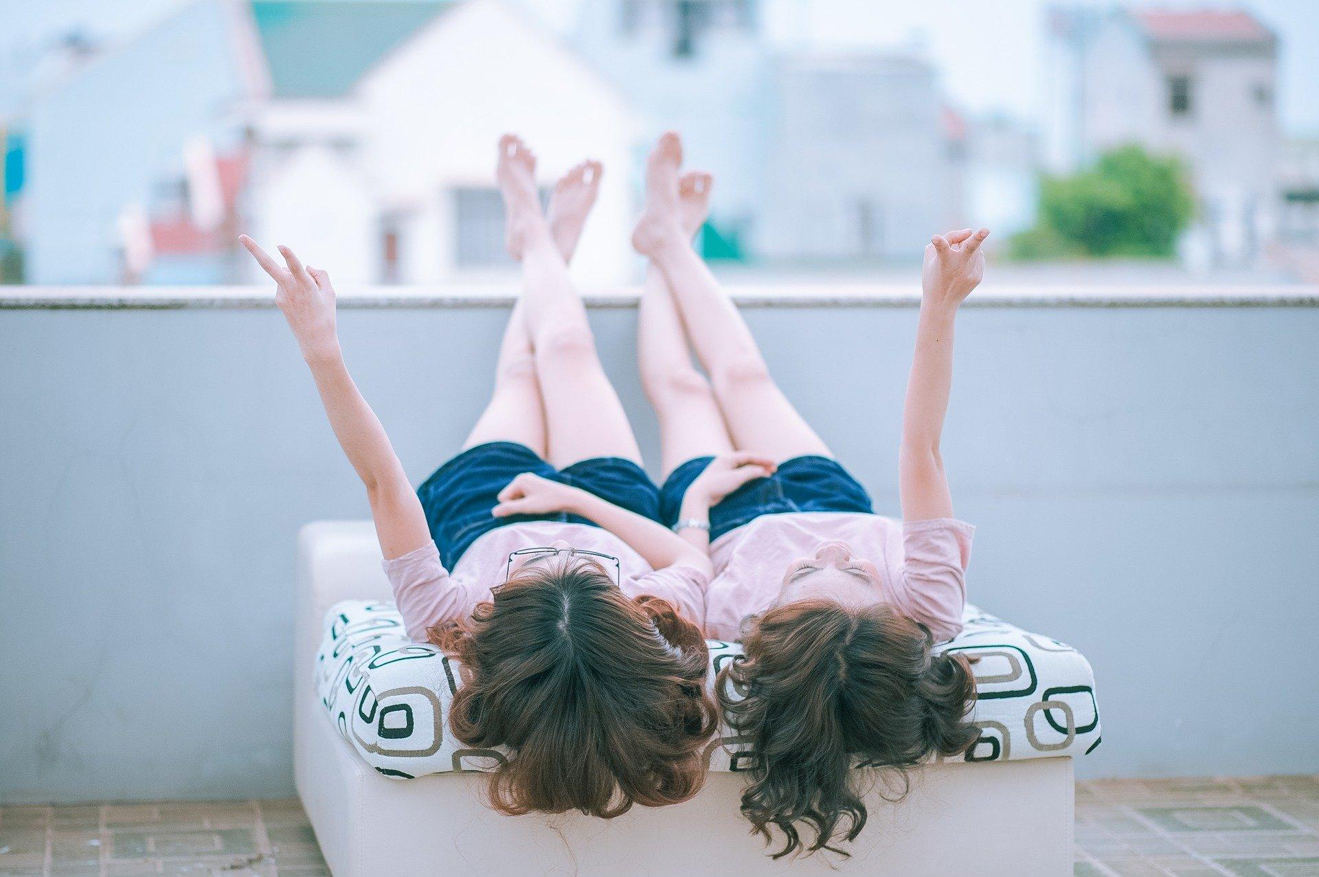 双子の子供が寝そべりながら手を上に上げている