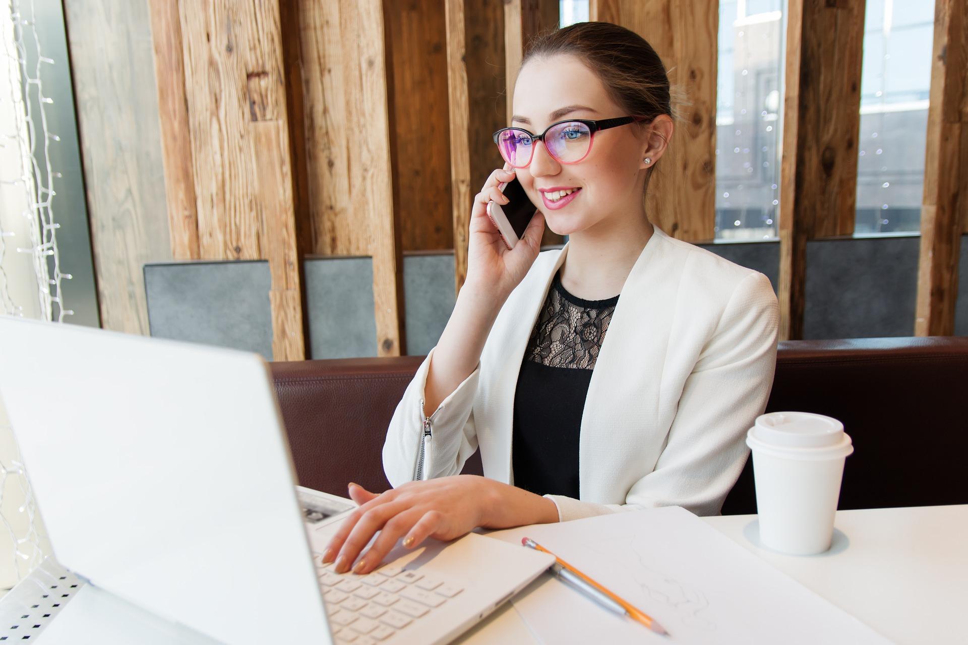 女性がパソコンを操作しながら電話をかけている