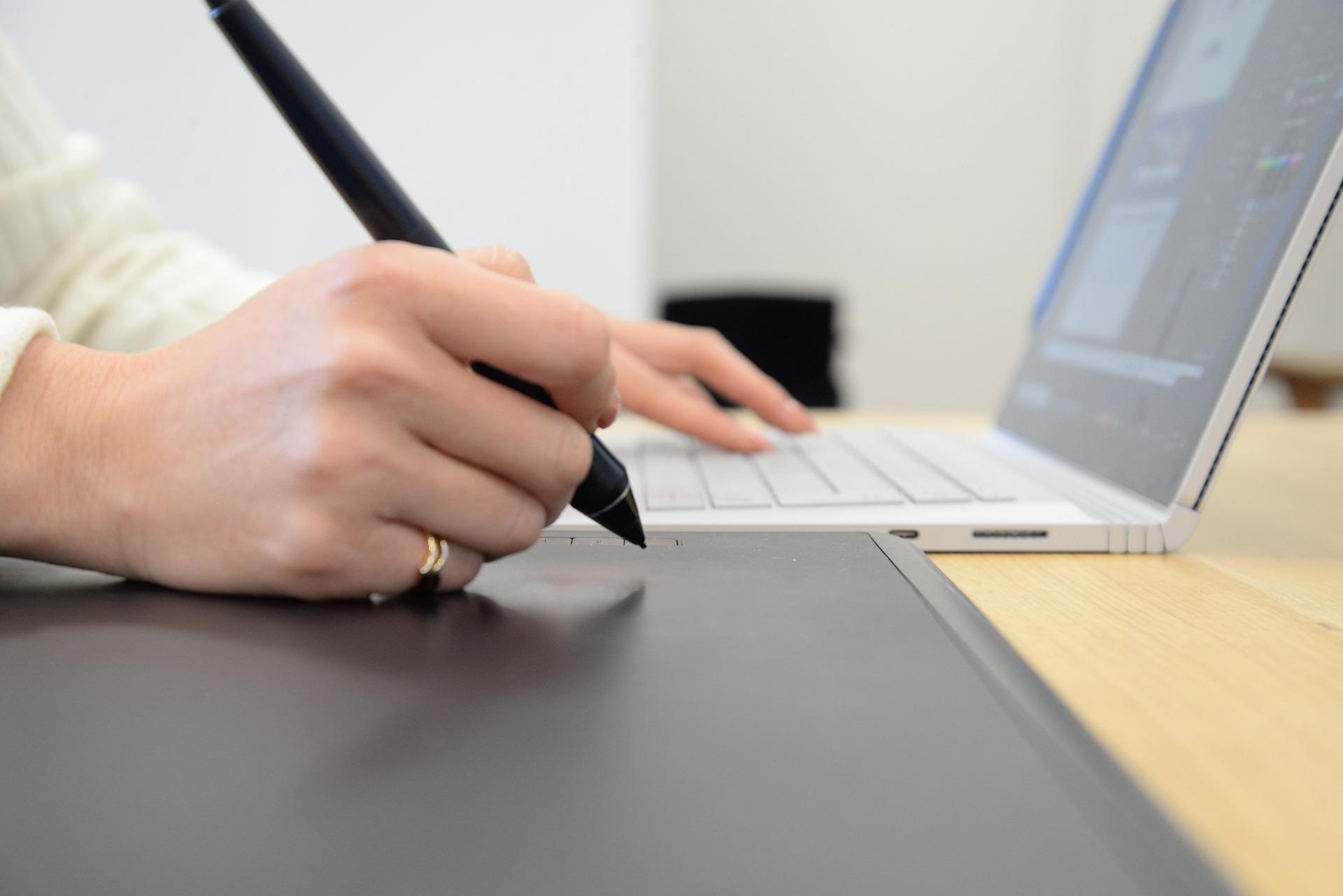 パソコンを操作しながら右手でメモを取っている手元