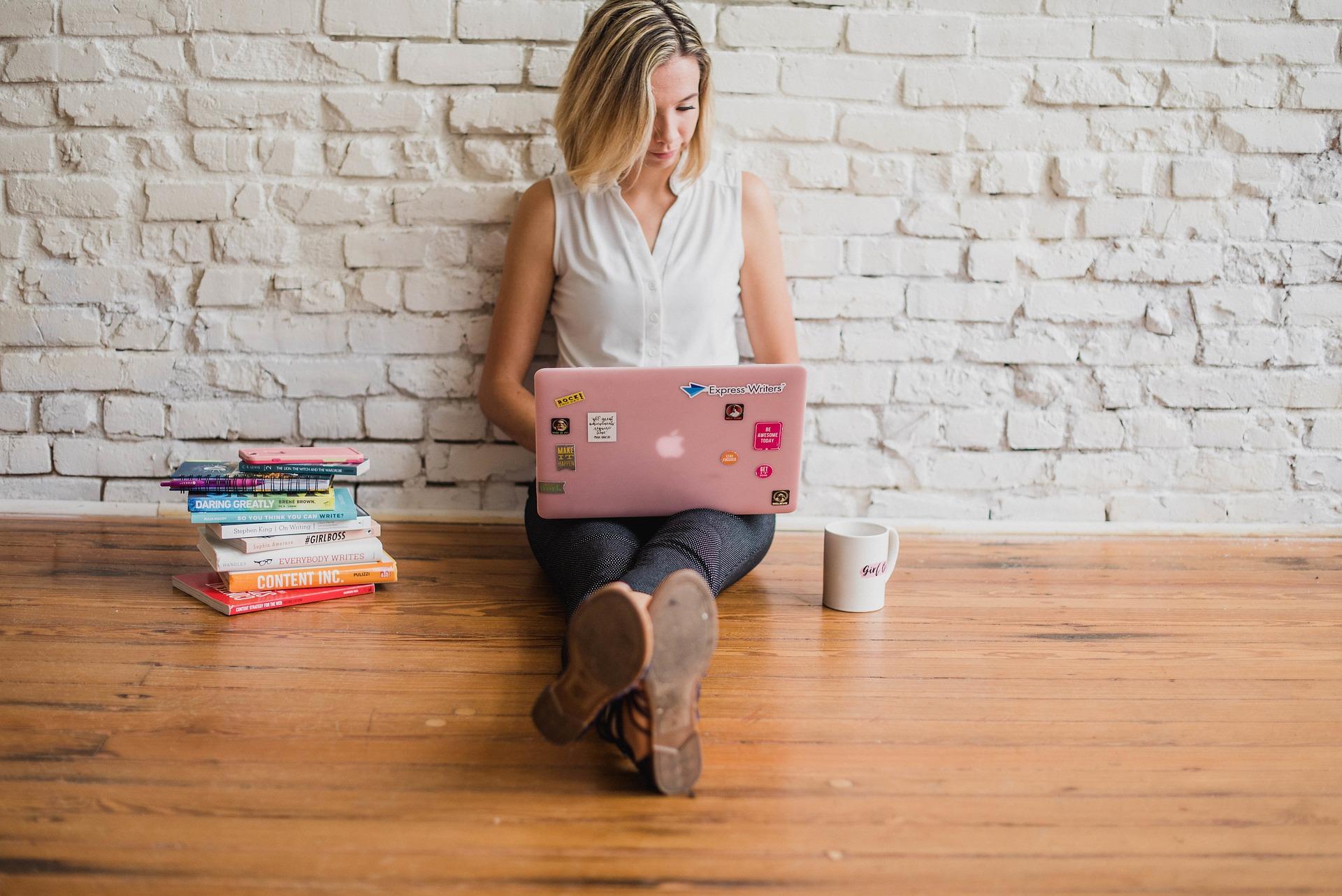 壁にもたれかかってパソコンを操作している女性