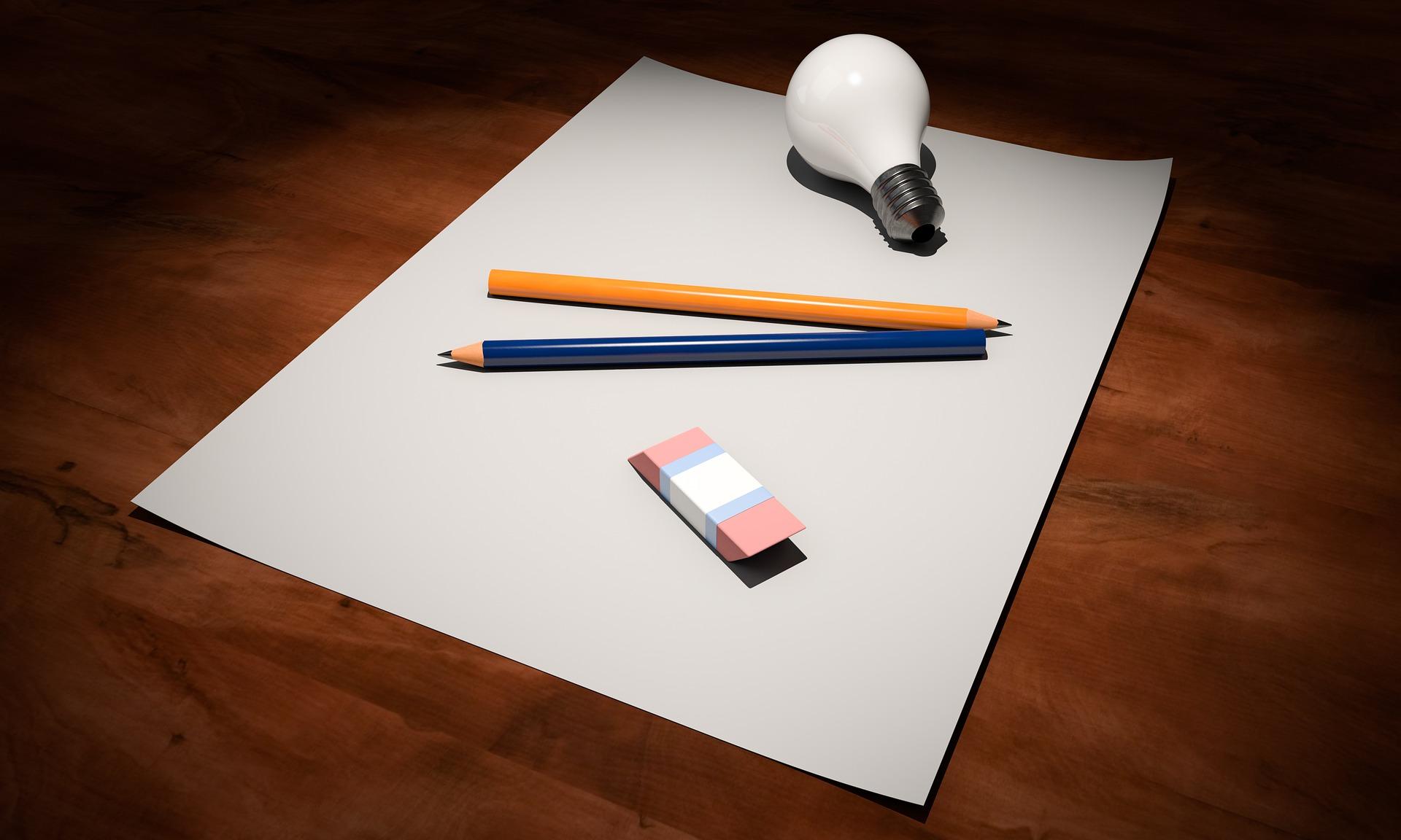 テーブルの上に紙と筆記用具が散らばっている