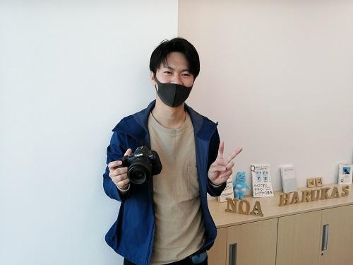 ノアのハルカス校にて一眼レフカメラを片手に笑顔でピースサインする葵健くん
