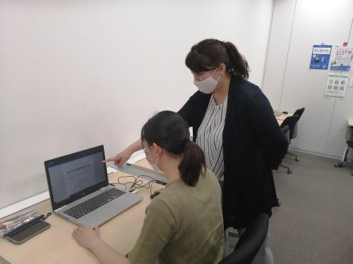 ノートパソコンの画面を指差して操作を教える先生