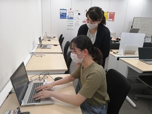 ノアの教室のノートパソコンに向かう瑛美ちゃんと、画面を覗き込んで見守る先生