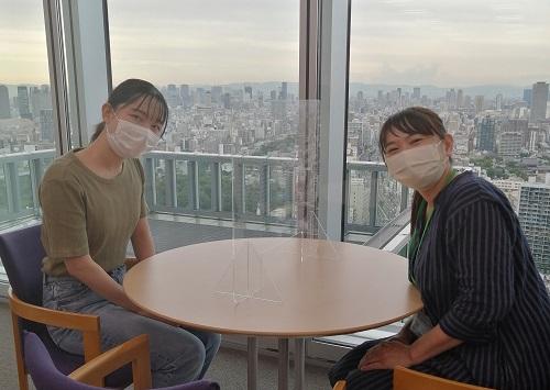 暮れなずむ大阪の街を見渡せるあべのハルカスの窓の前でカメラに向け笑顔を見せる瑛美ちゃんとしもの