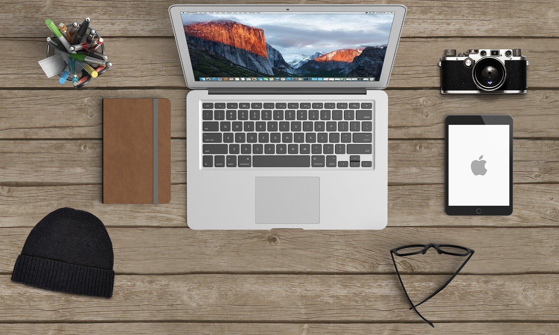 デスクの上のノートパソコンやその他のガジェットが広げられている