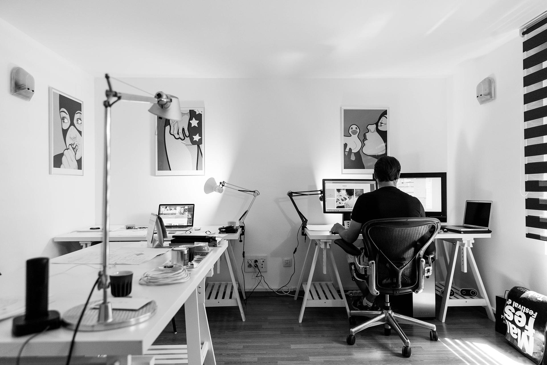 アトリエで絵を描いている男性の白黒写真