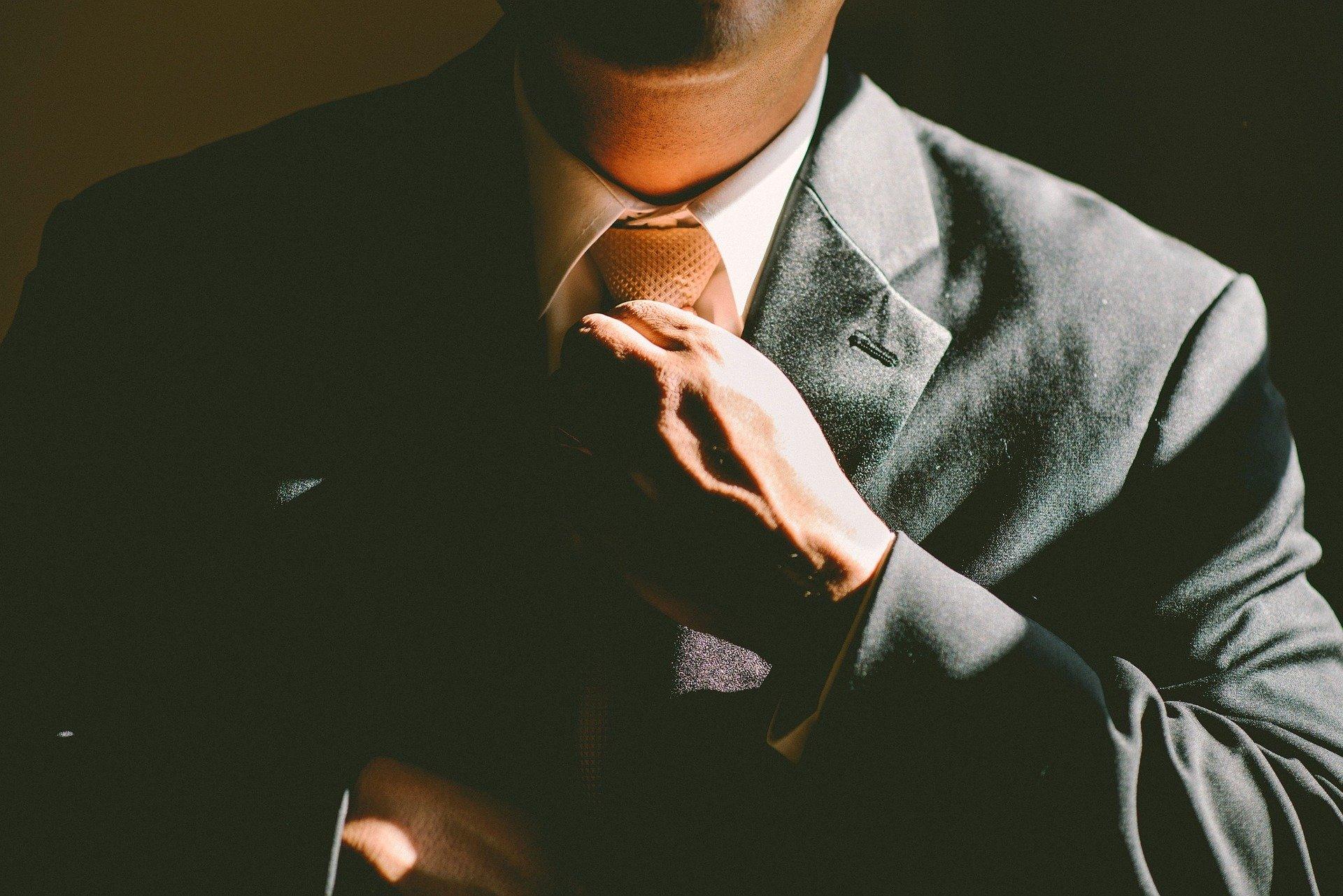 スーツのネクタイを締めている男性の首元