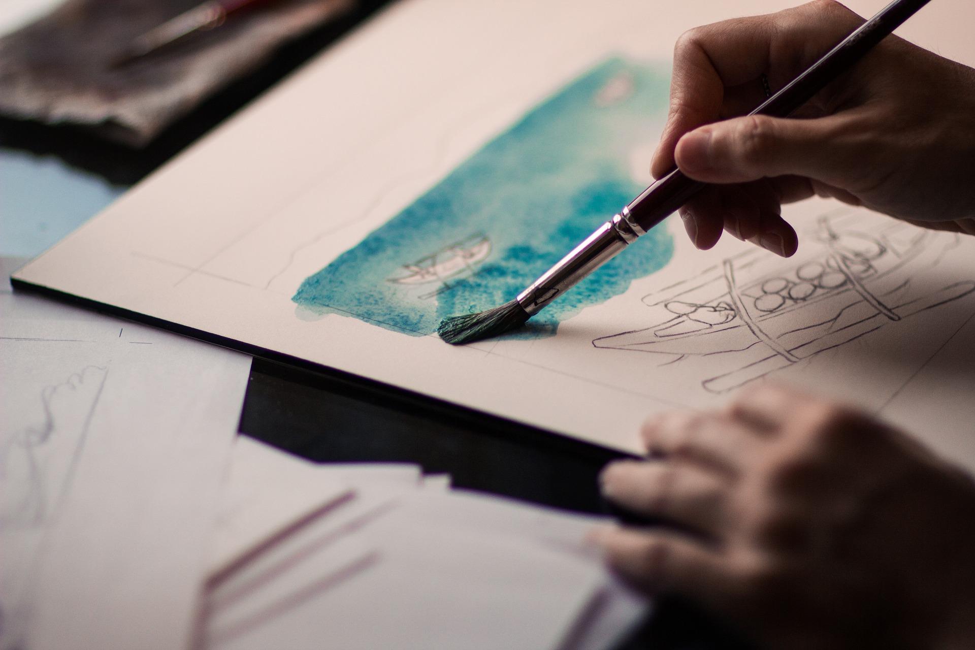 紙に筆で色を塗っている手元